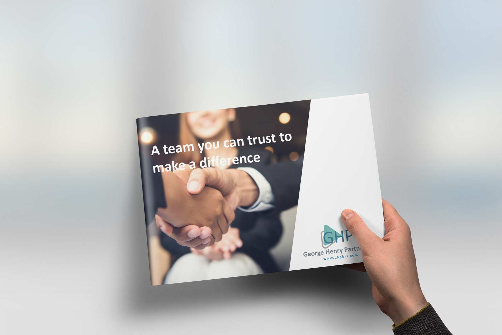 Hand is holding a sophisticated, well designed corporate brochure design over a blurred background